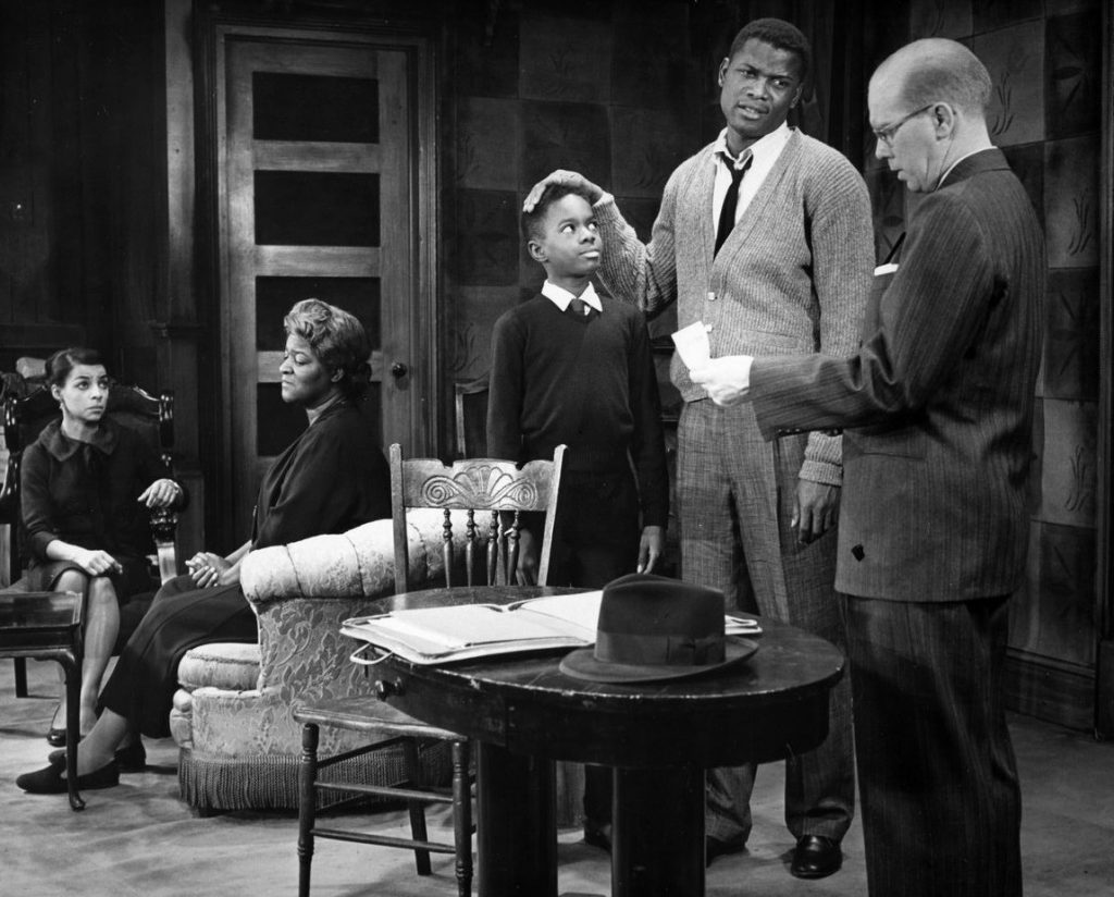 Photo of the stage production. The daughter and mother of the family sit in chairs whilst the sons talk to the lawyer.