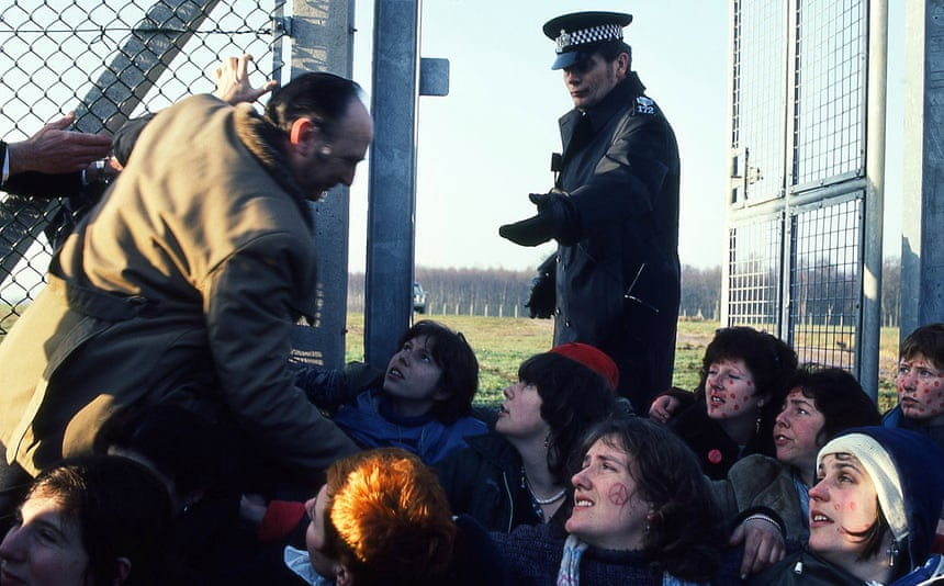 Several women are seated on the ground with peace signs whilst a man and a police man attempt to move them