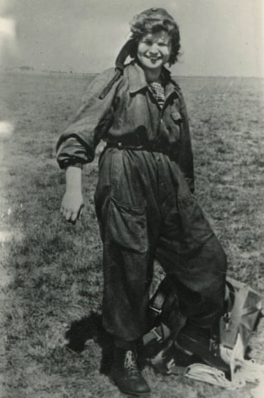 Valentina Tereshkova standing on the ground wearing a jumpsuit and and holding a parachute harness.